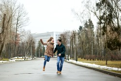 Two young people, wearing casual clothes and jeans, running and jumping, holding hands, laughing, smiling, in spring park