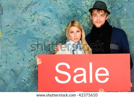 Two young people with advertisement board. Sale, shopping.
