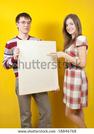 Two young people with white banner on yellow background