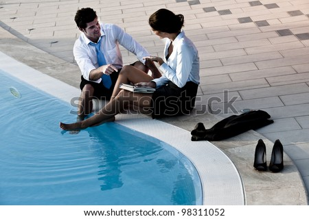 Photo of Two young people working free with feet in the pool
