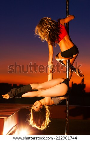 Two young pole dance women on urban background.