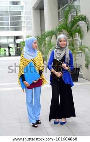 Two young pretty Asian muslim college girl with file and smile