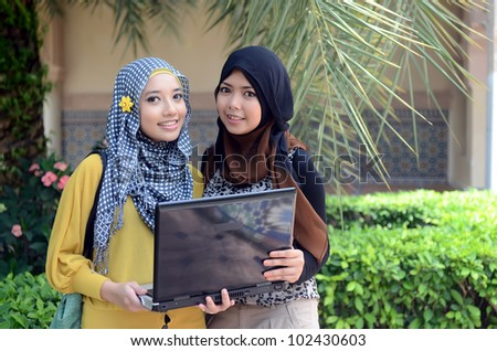 Two young pretty Asian muslim college girl with laptop and smile