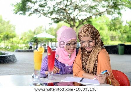 Two young pretty Asian muslim woman in head scarf study together