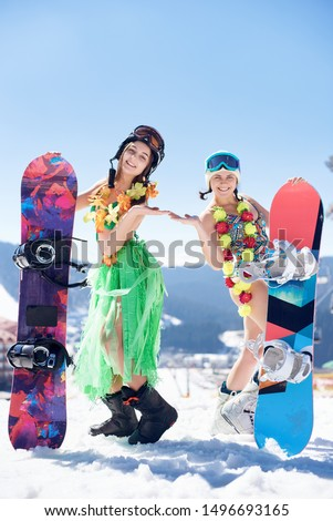 Two young pretty female snowboarders in swimsuit, bra, skirt and flower wreath decoration posing with snowboards on background of blue sky and winter mountain resort. Sports and festivity concept. #1496693165