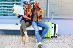 Two young pretty girls exploring and looking on map before their traveling adventures, smiling and having fun before new emotions. Best friend posing with their luggage.
