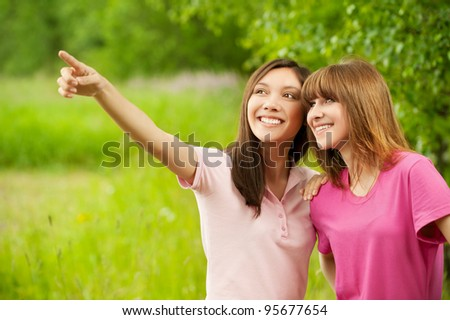 Two young pretty girls in a park one of them points at something