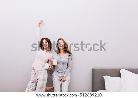 Two young pretty girls in pajamas with cups in sleeping room on grey wall background. They having fun and smiling to camera