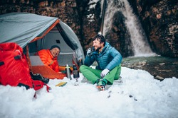 Two young professional male tourists are preparing food and hot drinks in the mountains near the river in winter. White waterfall and beautiful texture of rocks on background. Travel trekking  concept