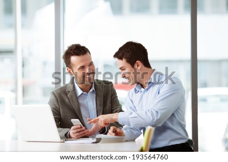 Two young professionals looking at a smartphone