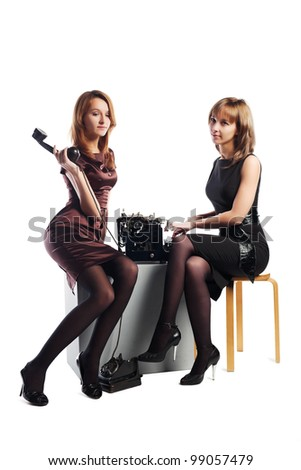 Two young retro secretaries with a typewriter and old phone