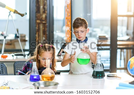 Two young scientists in protective glasses doing intereting chemical experiments with colored liquids and dry ice in beakers.