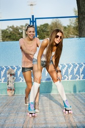 Two young sensual women skating in park, outdoors