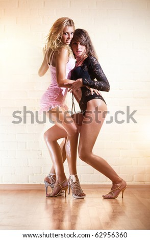 Two young sexy women. On wall background.