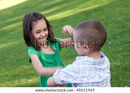 Two young siblings playfully hitting each other and rough housing.  Slight motion blur with sharp focus on the girls face.