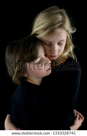 Two young sisters in a solemn, loving embrace