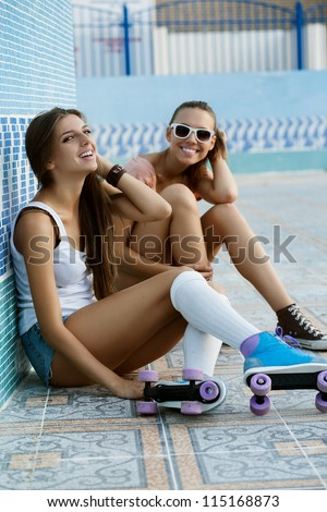 Two young skateboarding and roller skating girl friends sitting and laughing in empty swimming pool, outdoors