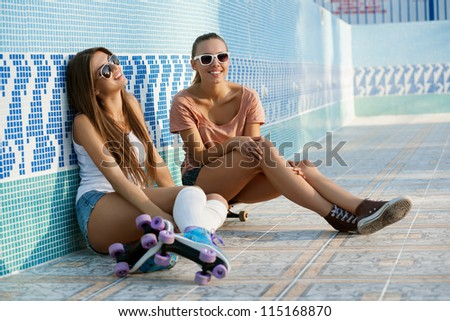 Two young skateboarding and roller skating girl friends sitting in empty swimming pool outdoors