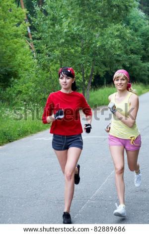 Two young slim women running on the road