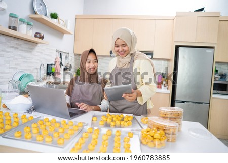 two young small muslim business owner selling homemade nastar cake from home. muslim woman baking pineapple tart together for eid mubarak