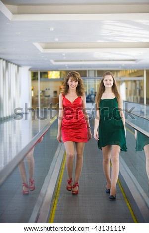Two young smiling beautiful women in some modern building.