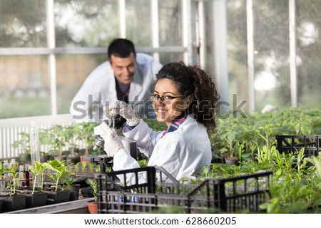 Two young smiling engineers working in greenhouse with sprouts. Plant protection and care concept ストックフォト ©