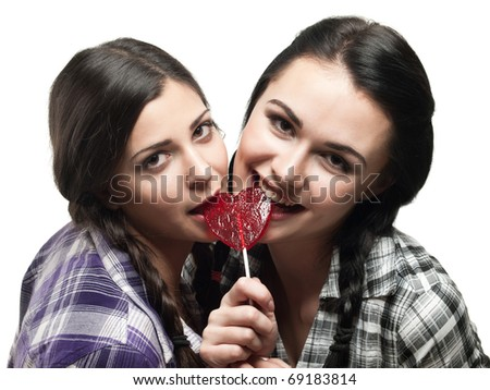 two young smiling girl with red heart lollipop isolated on white