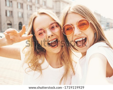 Two young smiling hipster blond women in summer white t-shirt clothes. Girls taking selfie self portrait photos on smartphone.Models posing on street background.Female showing positive face emotions ストックフォト ©