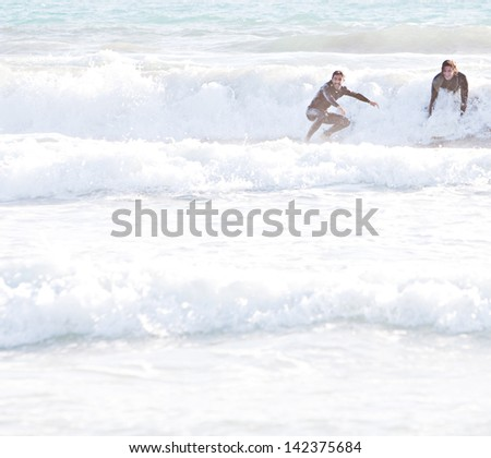 Two young sports surfer men starting to ride a wave, one standing up on his board while surfing on a sunny day during a summer vacation.
