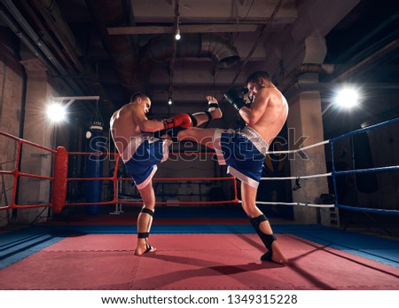 Two young sportsmen kickboxers training kickboxing in the ring at the sport club