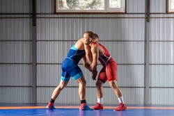 Two young sportsmens wrestlers in red and blue uniform wrestling against wrestling carpet, view side