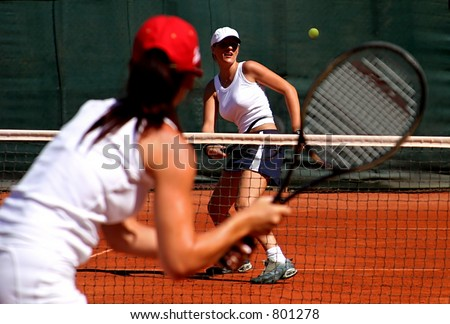 Two young sporty female tennis players enjoying a game in the sun on the Costa del Sol