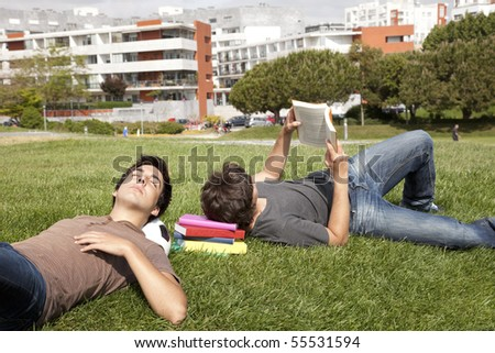 two young students sleeping at the grass over books and a soccer ball