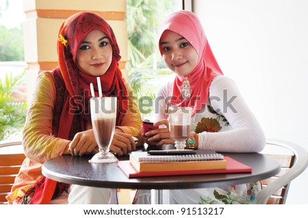 Two young stylish muslim women have a meet up at a cafe