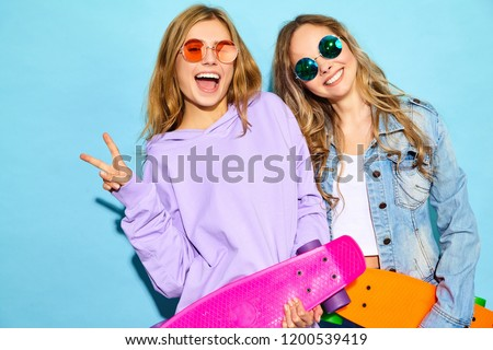 Two young stylish smiling blond women with penny skateboards. Models in summer hipster sport clothes posing near blue wall in studio. Positive girls going crazy