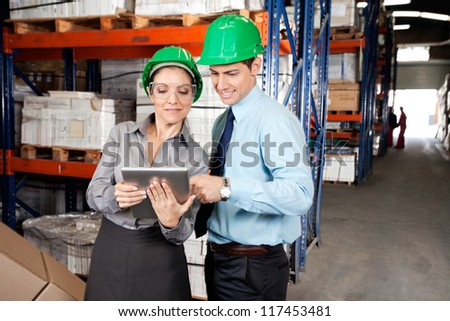 Two young supervisors in formalwear using digital tablet at warehouse - stock photo