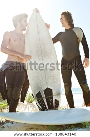 Two young surfer friends standing on the dunes of a white sand beach and getting ready for surfing with their surfing boards and wearing a neoprene rubber suit during a sunny day with a blue sky.