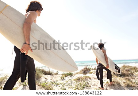Two young surfer friends walking towards the shore of a white sand beach carrying their surfing boards and wearing a neoprene rubber suit during a sunny day with a blue sky. - stock photo