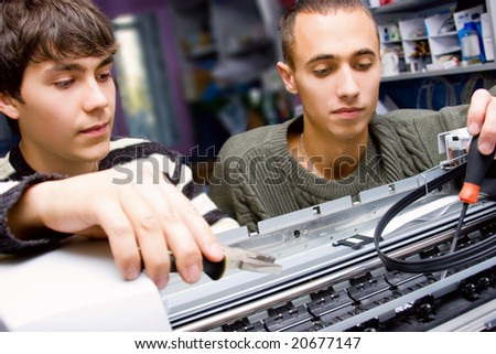 Two young technicians repairing printer