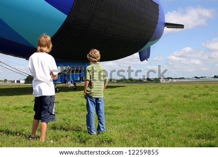 Two young teenage boys studying an airship as it swings o nits tether.