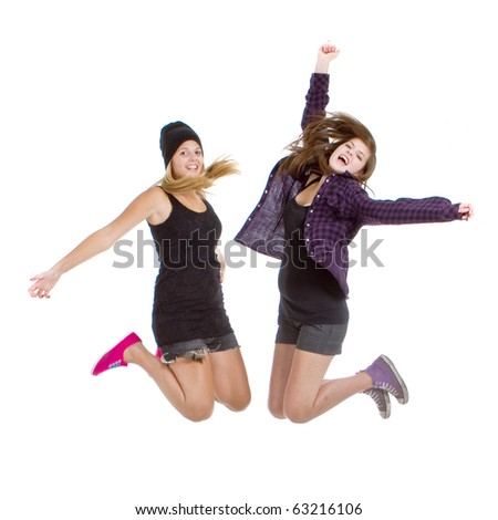 Two young teenage girls with trendy stylish clothes jumpingover white background.