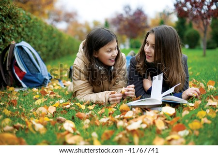 Two young teenage students reading in the park.