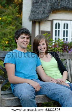 Two young teens smiling and sitting on a park bench outside
