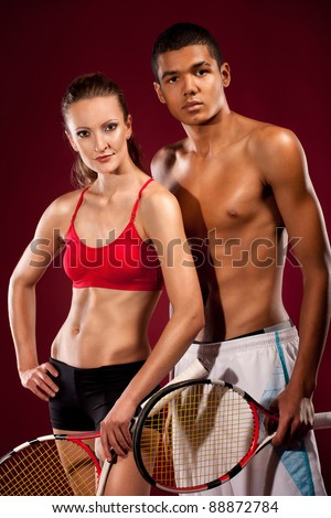 Two young tennis players standing with rackets in studio