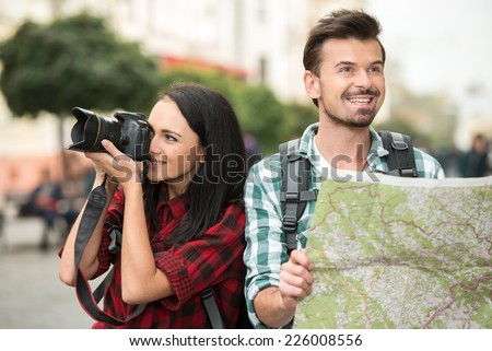 Two young tourists with backpacks, touristic map and camera. Sightseeing City.