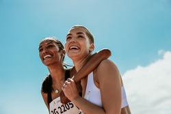 Two young woman athletes smiling outdoors. Female runners looking happy after winning the competition.