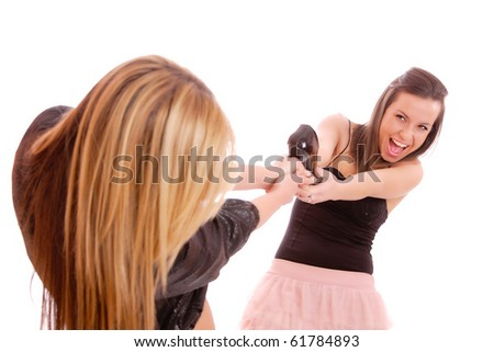 Two young woman fighting for a shoe over a white background