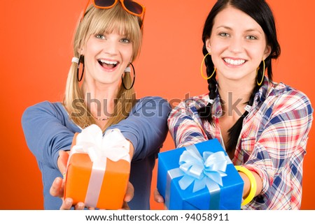 Two young woman friends hold party presents smiling orange background
