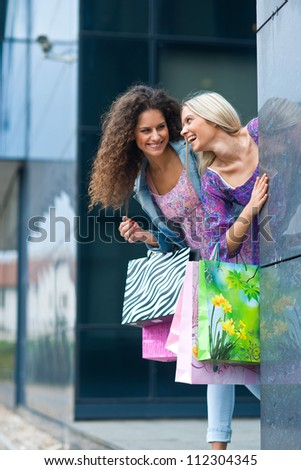two young woman friends with shopping bags smiling and having fun