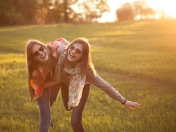 Two young woman making fun on nature at sunset